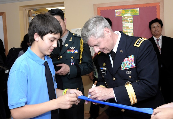 Army Gen. Walter L. Sharp chats with a student as he signs the ribbon he cut during the official opening of the new Casey Elementary School Sept. 15, 2010, at Camp Casey, South Korea. General Sharp is the commander of U.S. Forces Korea. (Courtesy photo/Yu Hu Son)