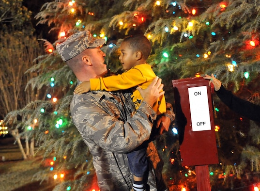 """3-year old Josiah Hawkins helps Col. Carl Buhler, 78th Air Base Wing commander, light the chapel Christmas tree. Team Robins conducted its annual Christmas Tree and Menorah Lighting Ceremony Tuesday. The event featured musical selections from the Veterans High School and Matt Arthur Elementary School choruses, a guest appearance by Santa Claus, and the reading of """"T'Was the Night Before Christmas"""". U. S. Air Force photo by Tommie Horton"""