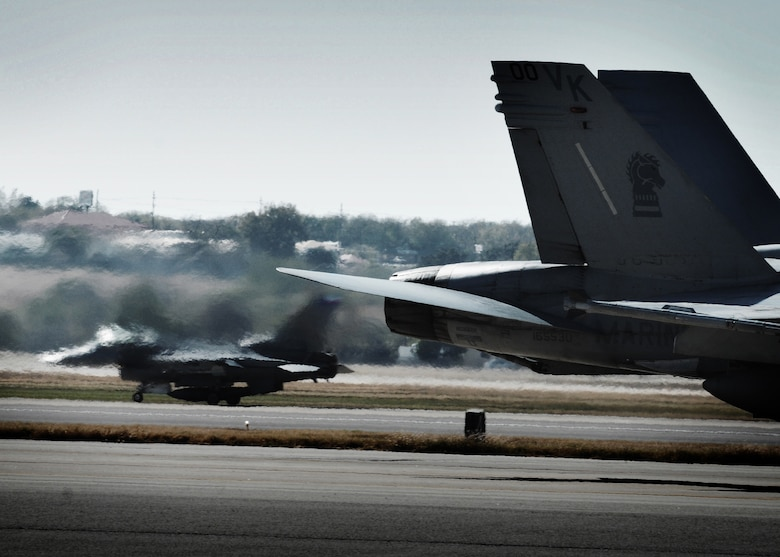 The jet wash from an F/A-18 Hornet from Marine Corps Air Station Miramar, California, blurs the view of an F-16 assigned to the Texas Air National Guard's 149th Fighter Wing. The two units participated in a joint training exercise at Kelly Field, Lackland Air Force Base, Texas, December 3, 2010.(U.S. Air Force photo/Staff Sgt. Eric L. Wilson)