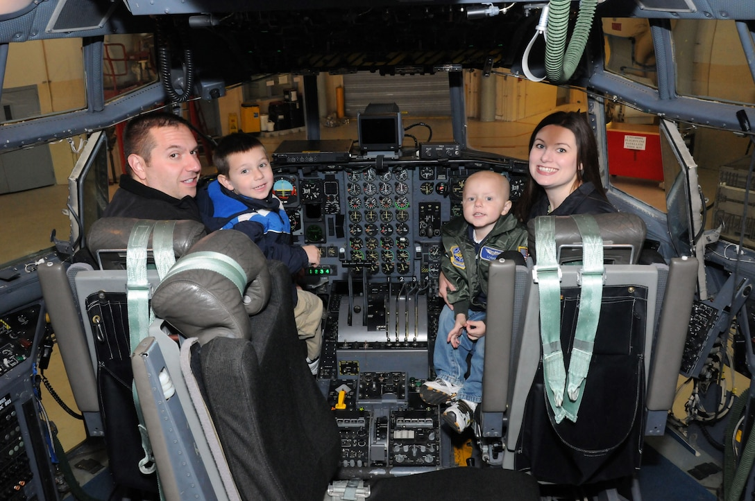 A local 3-year-old boy's dream came true when he reported to the 107th Airlift Wing for the day as an honorary pilot. Logan and his family check out all the gauges, switches and gadgets in the cockpit of a C-130. From left to right; Logan's father Marc, his brother Caiden, and his mother Carol.  (U.S. Air Force photo/Staff Sgt. Peter Dean)
