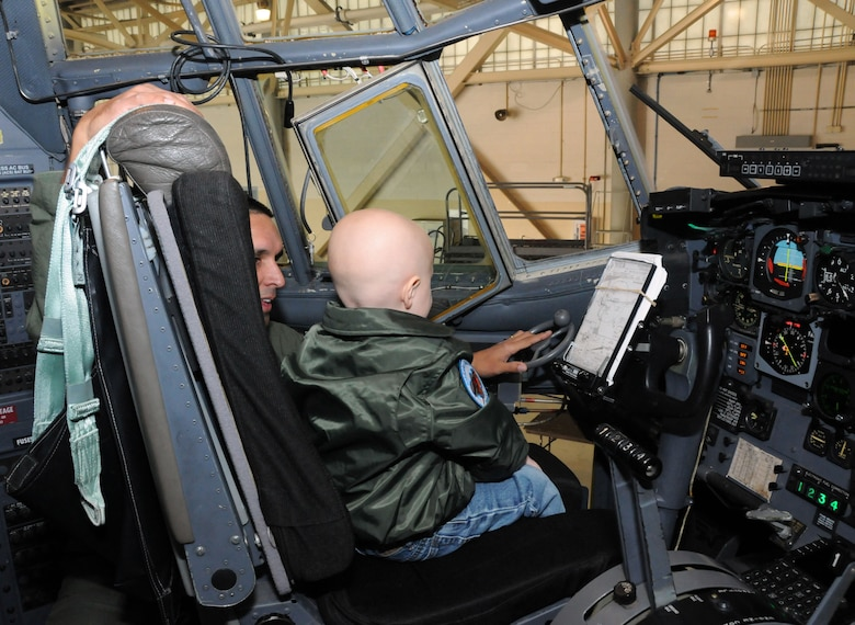 A local 3-year-old boy's dream came true when he reported to the 107th Airlift Wing for the day as an honorary pilot. Maj. Michael Galvin shows Logan the gadgets in the cock pit of a C-130. (U.S. Air Force photo/Staff Sgt. Peter Dean)