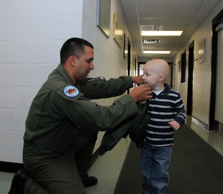 A local 3-year-old boy's dream came true when he reported to the 107th Airlift Wing for the day as an honorary pilot. Maj. Michael Galvin presents Logan with his very own flight jacket that included the appropriate patches. (U.S. Air Force photo/Staff Sgt. Peter Dean)