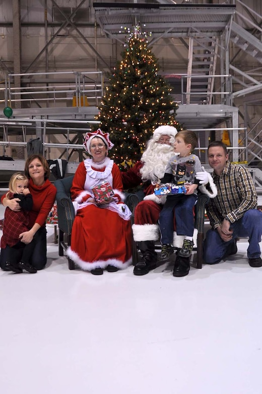 Family members and Airmen from the 128th Air Refueling Wing, Milwaukee, pose with Santa and Mrs. Claus during the annual holiday party on Saturday, Dec. 4, 2010.  From left are daughter Madelyn Mielcarek, mother Master Sgt. Jennifer Mielcarek, son Mason and father Capt. Tom Mielcarek.  The holiday party was hosted by the Airman and Family Readiness Program, and over 300 Airmen, military spouses and children attended.  U.S. Air Force photo by Staff Sgt. Jeremy Wilson / released