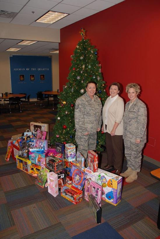 Chaplain Erica A. Bell, Mrs. Betty Gaskins and Technical Sergeant Judi L Zummach of the 164th Security Forces Squadron gather around some of the gifts donated by members of the 164th Airlift Wing for the Project Toy Soldier Campaign.