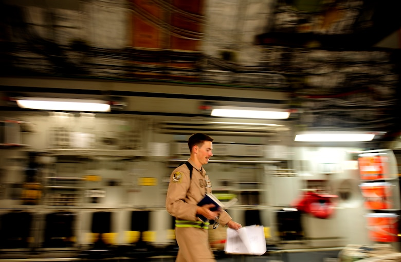 Airman 1st Class David Schmitz, a C-17 Globemaster III aircraft loadmaster assigned to the 816th Expeditionary Airlift Squadron at a non-disclosed base in Southwest Asia, walks back to his station after completing paperwork for a Marine Corps M1A1 Abrams tank being brought to Afghanistan on Nov. 28, 2010. (U.S. Air Force Photo/Staff Sgt. Andy M. Kin)