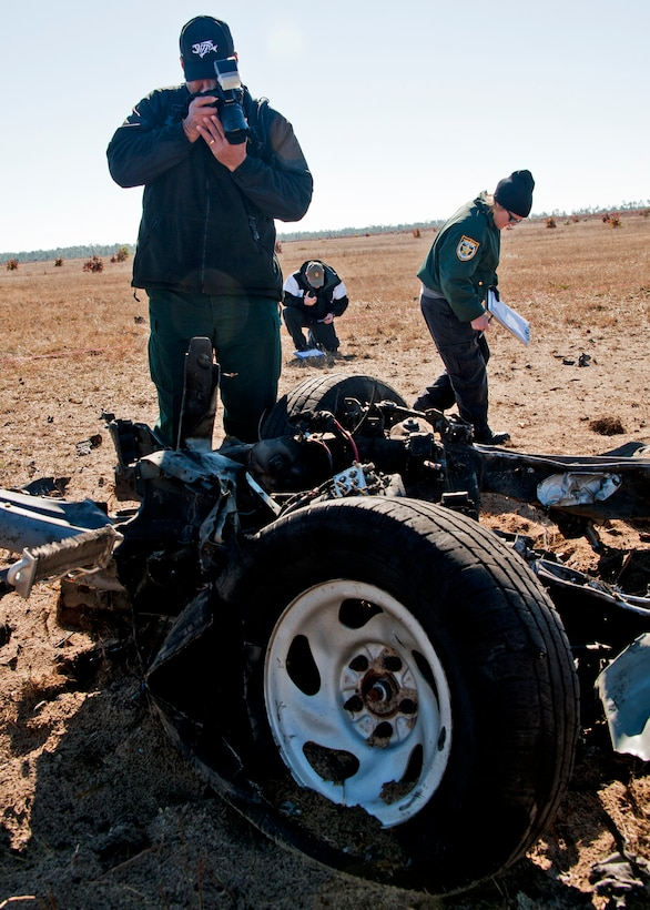 Detective William Punausuia, Leon County Sheriff's Department, photographs the wreckage of a pickup truck, while team leader, Sgt. John Corley, Bay County Sheriff's Department, takes notes during the investigation of a created crime scene Dec. 1 at  Eglin Air Force Base, Fla.  The investigations were part of the FBI's large vehicle post blast school attended by state and local law enforcement agencies as well as Marine and Air Force explosive ordnance disposal technicians. Three vehicles were blown up to create the crime scenes that students would investigate.  This was the largest class held in the U.S. and the first ever here.(US Air Force photo/ Samuel King)