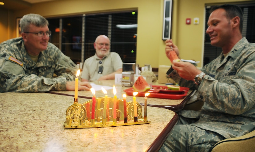 "SOTO CANO AIR BASE, Honduras --  Chaplain (Capt.) Paul Cartmill, Mr. Bruce Drube and Chaplain (Capt.) Charles Seligman enjoy a meal together at the base dining facility after completing the ceremonial lighting of the Menorah during the Chanukah celebration Dec. 6. From the Hebrew word for ""dedication"" or ""consecration,"" Hanukkah marks the rededication of the Temple in Jerusalem after its desecration by the forces of the King of Syria. (U.S. Air Force photo/Tech. Sgt. Benjamin Rojek)"