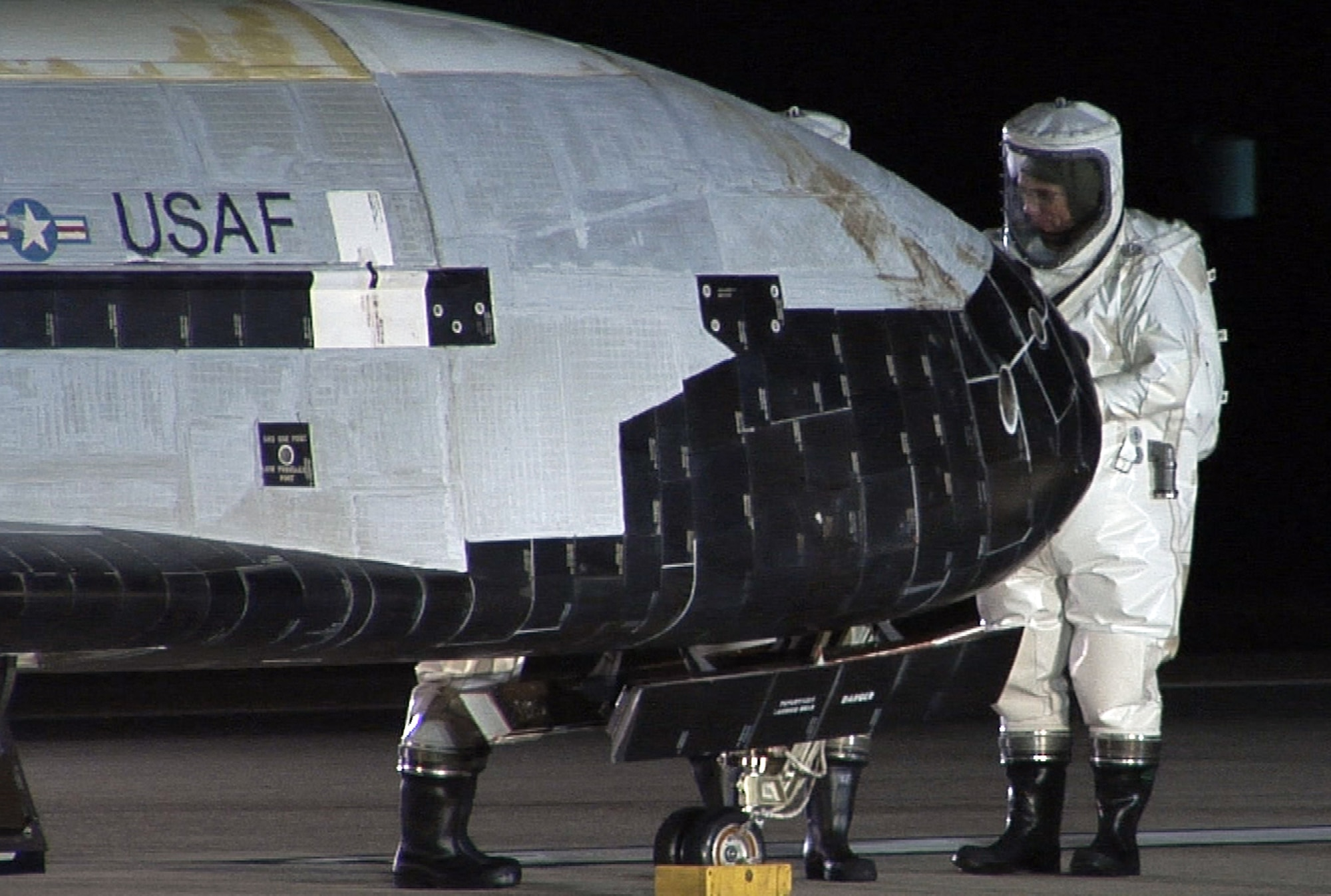 The X-37B Orbital Test Vehicle sits on the runway at Vandenberg Air Force Base, Calif., Dec. 3, 2010, during post-landing operations. Personnel in self-contained atmospheric protective ensemble suits are conducting initial checks on the vehicle and ensuring the area is safe. The X-37B launched April 22 from Cape Canaveral, Fla., allowing teams to conduct on-orbit experiments for more than 220 days during this first mission. (U.S. Air Force photo/Michael Stonecypher)