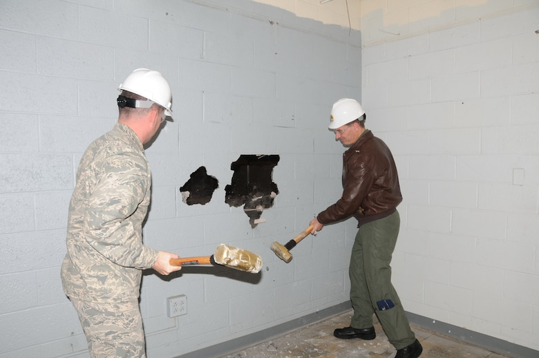 """Lt. Col. Jerry McDonald (left), commander of the 103rd Maintenance Group, and Col. Frank Detorie, 103rd Airlift Wing commander, take swings at a wall on the west side of the main hangar at Bradley Air National Guard Base in East Granby, Conn. on Wednesday, Dec. 1, 2010. The """"wall breaking"""" took place following a ceremony marking the start of a renovation project that will help ready the unit for its next mission flying the C-27J Spartan. (U.S. Air Force photo by Tech. Sgt. Erin E. McNamara)"""