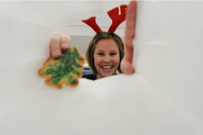 Rose Sharp drops a holiday cookie into a bag during the annual the Team Charleston Spouses' Club Cookie Drop at Joint Base Charleston-Air Base, S.C., Dec. 8, 2010. This year, the TCSC put together more than 500 bags and boxes of holiday cookies for service members living in the base dormitories, eating at the dining facility and who are deployed. Ms. Sharp is the president of the TCSC. (U.S. Air Force photo/James M. Bowman)
