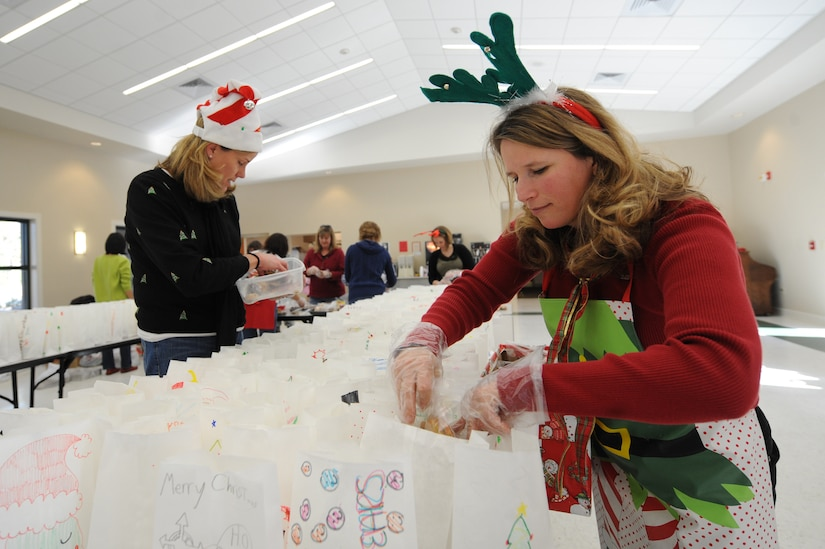 Joan Tufts, right, and Jane Holba place cookies in bags during the annual Team Charleston Spouses' Club Cookie Drop at Joint Base Charleston-Air Base, S.C., Dec. 8, 2010. This year, the TCSC put together more than 500 bags and boxes of holiday cookies for service members living in the base dormitories, eating at the dining facility and who are deployed. Mrs Tufts is wife of Maj. Adam Tufts with the 14th Airlift Squadron, and Mrs. Holba is the wife of Col. Robert Holba who is the 437th Operations Group commander. (U.S. Air Force photo/James M. Bowman)