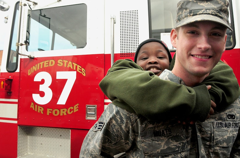 """William Goodwin rides piggy-back with his """"buddy"""" Senior Airman Corey Moats at the base fire department during a school tour Dec. 2, 2010, on Joint Base Charleston-Air Base, S.C. William and fellow classmates from Memminger Elementary School paired-up with students enrolled at the base's Airman Leadership School during the tour of the base. For the children, the event provided a chance to learn about military life and history. For the Airmen, it was an opportunity to mentor and give back to the local community. (U.S. Air Force photo/Staff Sgt. Daniel Bowles)"""