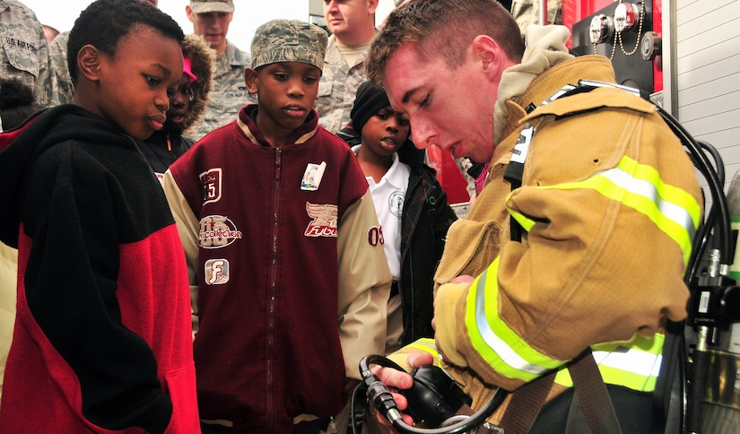 Lorenzo Simmons, left, and C.J. Pinckney listen in and learn about fire safety from Senior Airman Samuel Siewert during a base tour Dec. 2, 2010, on Joint Base Charleston-Air Base, S.C. At the fire house, children toured the fire engines and main building as fire fighters familiarized the students with equipment and practices used during emergency response. Lorenzo and C.J. were joined by third-grade classmates from Memminger Elementary School as well as students enrolled in the base's Airman Leadership School. Airman Siewert is a fire protection journeyman with the 628th Civil Engineer Squadron. (U.S. Air Force photo/Staff Sgt. Daniel Bowles)