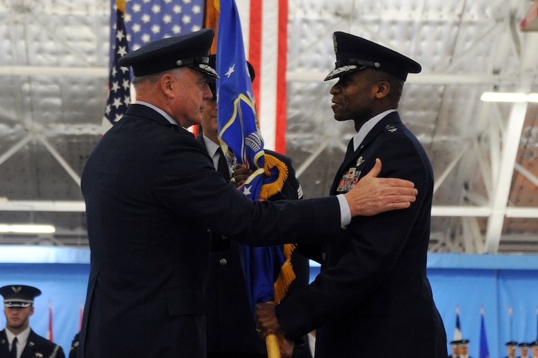 """Air Force Vice Chief of Staff Gen. Carrol H. """"Howie"""" Chandler congratulates Maj. Gen. Darren W. McDew, the new Air Force District of Washington commander, after passing him the unit guidon during a change of command ceremony at Andrews Air Force Base, Md., on Dec. 9, 2010.  General McDew's prior assignment was at the Pentagon, where he was the vice director of Strategic Plans and Policy on the Joint Staff. (U.S. Air Force photo/Senior Airman Melissa V. Brownstein)"""