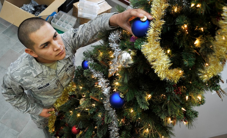 Airman Marc Holguin, 460th Space Communications Squadron puts ornaments on a Christmas decorated tree. Many of buckley's units are beginning to join in on the Christmas celebration.(U.S. Air Force photo by Airman 1st Class Paul Labbe.)