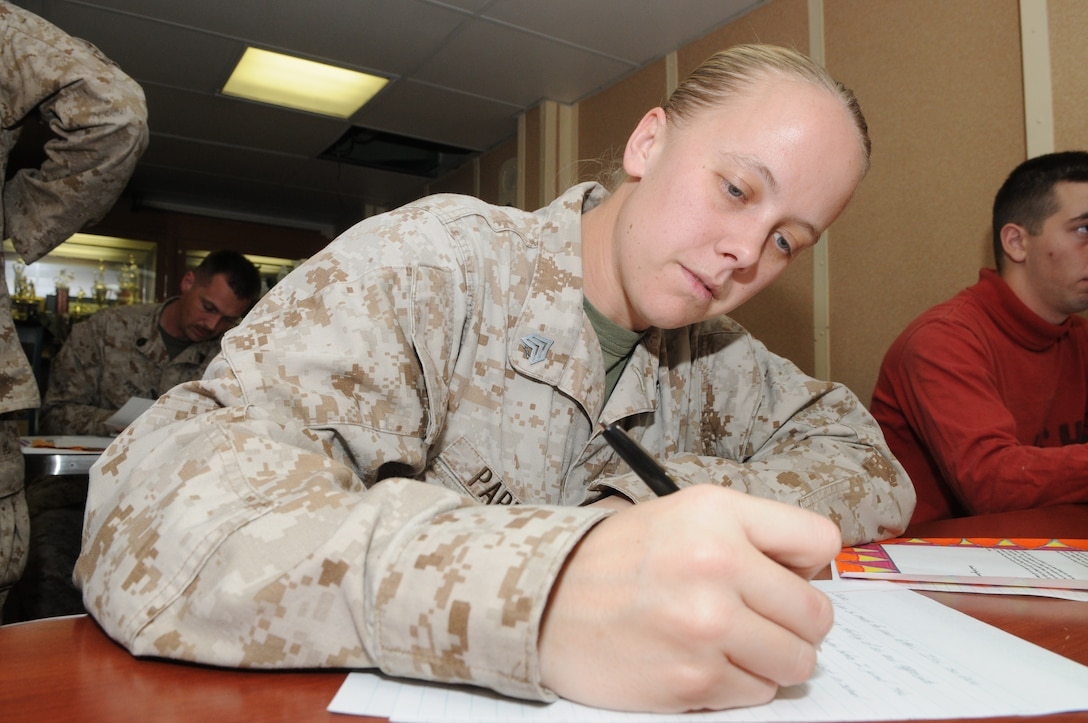 """Sergeant Deanna Parker with Combat Logistics Battalion 26, 26th Marine Expeditionary Unit, responds to a letter written by an elementary school student at Assumption Catholic School in O'Fallon, MO. 26th MEU Marines and sailors aboard USS Kearsarge volunteered to respond to 88 letters sent from Assumption Catholic and North Asheville Christian School in Asheville, N.C. """"These letters are very encouraging, and it will be something that I will keep forever,"""" said Parker. """"One thing the girl put in the letter really stood out to me: 'give someone a hand and you will both climb higher.' I could just tell the girl who wrote this really put some thought into it."""""""