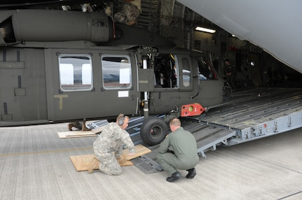 SOTO CANO AIR BASE, Honduras --  Using plywood squares, a member of the 1-228th Aviation Regiment and an aircrew member from McChord AFB, Wash., ensure a Black Hawk helicopter clears the loading ramp as it's taken out of a C-17 Globemaster III here Dec. 9. (U.S. Air Force photo/Tech. Sgt. Benjamin Rojek)