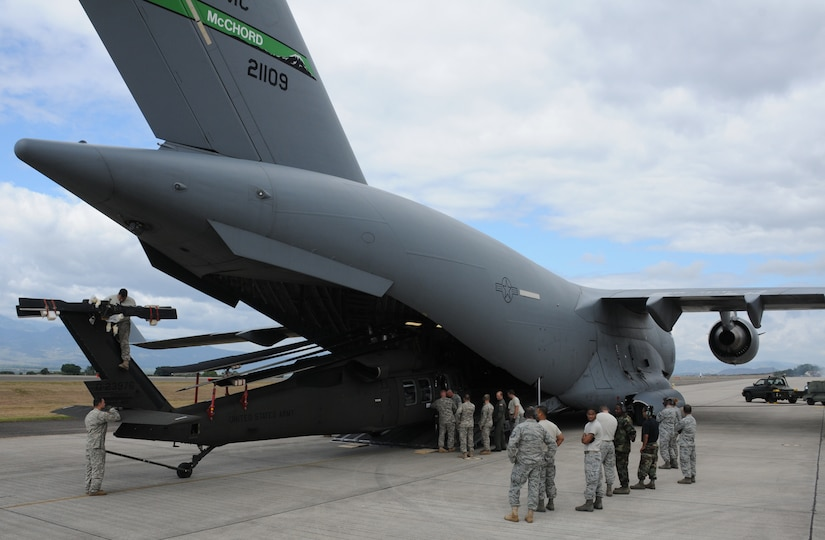 SOTO CANO AIR BASE, Honduras --  Members of Joint Task Force-Bravo watch as a Black Hawk helicopter is unloaded from a C-17 Globemaster III here Dec. 9. The C-17, which is from McChord AFB, Wash., delivered the helicopter after it received repairs in the U.S. (U.S. Air Force photo/Tech. Sgt. Benjamin Rojek)