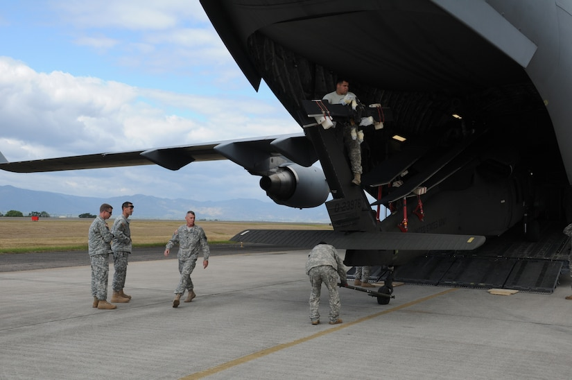SOTO CANO AIR BASE, Honduras --  Checking to make sure they're clearing the ramp, members of the 1-228th Aviation Regiment pull a Black Hawk helicopter from inside a C-17 Globemaster III here Dec. 9. The helicopter, which was delivered by the C-17 out of McChord AFB, Wash., was returned to Soto Cano after receiving repairs in the U.S. (U.S. Air Force photo/Tech. Sgt. Benjamin Rojek)