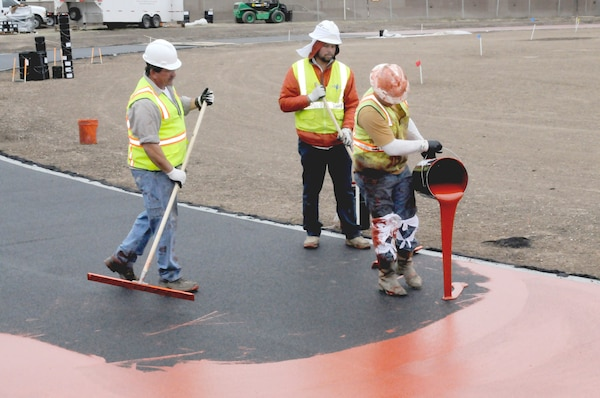 Will Cordell (right), Texas Sports Builders employee, pours seal coat on the Rambler Fitness Center's new synthetic quarter-mile running track while his coworkers Johnny Daniel (left) and Aldo Domingues prepare to spread the coating.