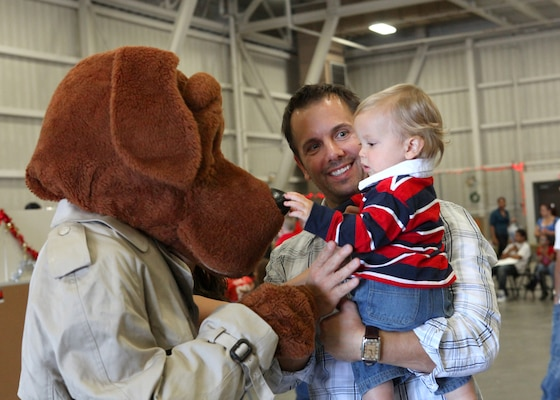 McGruff the Crime Dog greets James Shappell, a civilian employee with the 344th Training Squadron, and his son, Josh, during the Lackland Children's Holiday Party. The base-wide event was held Dec. 4 at the 344th TRS. (U.S. Air Force photo/Robbin Cresswell)