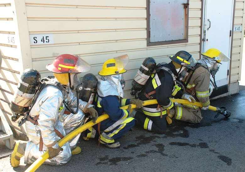 SOTO CANO AIR BASE, Honduras - Firefighters from the U.S., Honduras and El Salvador prepare to breach the structural fire training building here, 8 Dec., during the landmark firefighting training exercise known as Central America Sharing Operational Knowledge and Experiences. CENTAM SMOKE is a week-long, quarterly event designed to enhance firefighting capabilities throughout Central America. (U.S. Air Force photo by Capt. John T. Stamm)