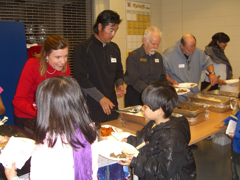 Volunteers serve a holiday meal during the Pearl S. Buck Christmas Party at Osan Dec. 4. (Courtesy photo)