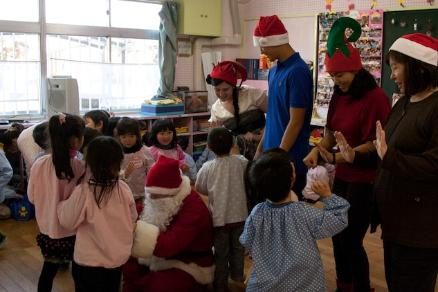 Santa, Pfc. Michael Hicks, and his helping elves, Sgt. Anne Laha, Lance Cpl. Vincent Wong and Lance Cpl. Michelle Thach say, goodbye to the Japanese children of Josho Hoikuen school in Iwakuni, Japan. As the children said goodbye, they gave high fives to the Marines.