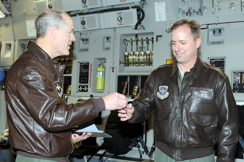 Air Force Lt. Gen. Allen G. Peck hands the keys to Col. John Wood after delivering the newest C-17A to the 437th Airlift Wing, Charleston, S.C., Dec. 9, 2010. The arrival of the aircraft brings the total number of C-17s assigned to the wing to 58. General Peck is the Air University commander and Colonel Wood is the 437 AW commander. (U.S. Air Force photo/Staff Sgt. Marie Brown)