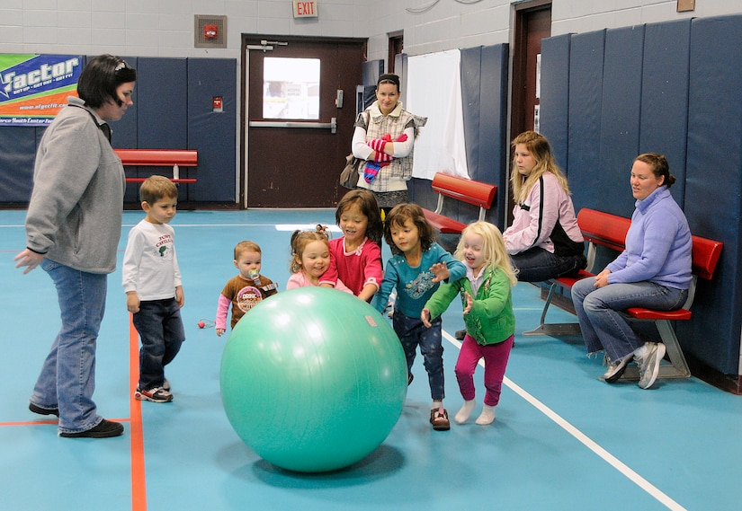 Children push an exercise ball at the Youth Center on Joint Base Charleston - Air Base during a Military Moms weekly meeting December 9, 2010. The Military Moms group is made up of more than 150 active participants with the goal of helping military moms acclimate to the military lifestyle. (U.S. Navy photo/Mass Communication Specialist 1st Class Jennifer R. Hudson)