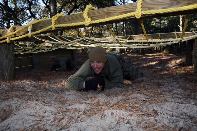Staff Sgt. Joseph Cusimano, a native of Sulphur, La., and an ammunition technician at Marine Corps Training Advisory Group, makes his way through the belly crawl obstacle during a MCTAG team building competition, Dec. 15 2010. Marines faced freezing temperatures to complete the obstacle course.