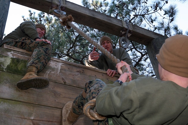 """Gunnery Sgt. John Jones, supply chief at MCTAG and Master Sgt. Charles Hermann, administration chief at MCTAG, are ready to lend a helping hand to one of their teammates during the """"Storming the Castle"""" obstacle during the obstacle course competition here, Wednesday."""