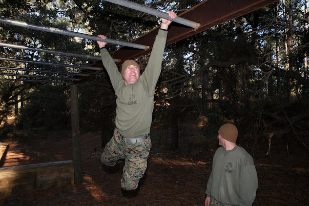 """Master Sgt. Charles Hermann, administration chief at MCTAG does his best """"George of the Jungle"""" expression while completing the """"Tarzan"""" monkey bars while going through the JEB Little Creek-Fort Story obstacle course, Wednesday."""