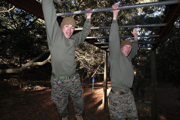 """Staff Sgt. Joseph Cusimano, a native of Sulphur, La., and an ammunition technician at MCTAG, and Gunnery Sgt. John Jones, a native of Ft. Myers, FL. and supply chief at MCTAG, swing through the """"Tarzan"""" monkey bars at the JEB Little Creek-Fort Story obstacle course, Wednesday."""
