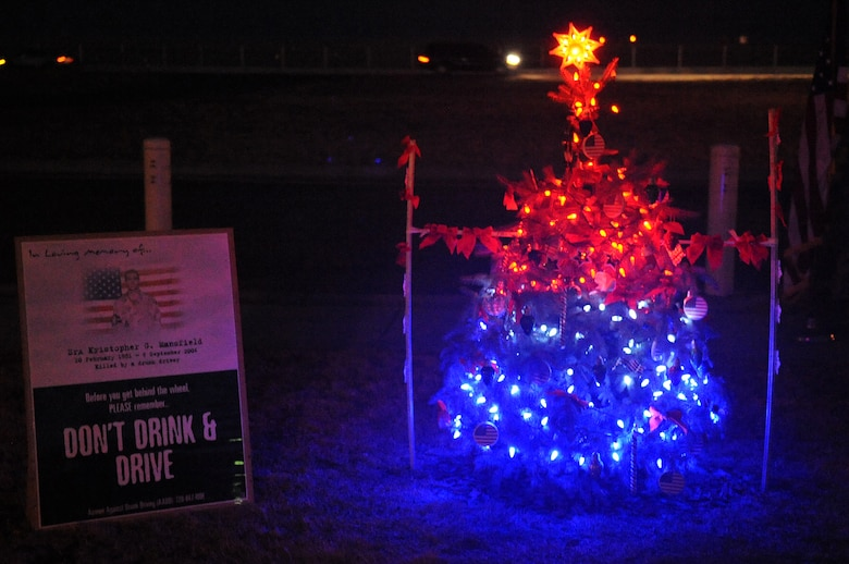 BUCKLEY AIR FORCE BASE, Colo.-- A Christmas tree is lit outside of the 460th Space Communications Squadron on Dec. 14, 2010 in honor of Senior Airman Kristopher Mansfield. Airman Mansfield was killed in 2004 by a drunk driver. (U.S. Air Force photo by Airman Manisha Vasquez)