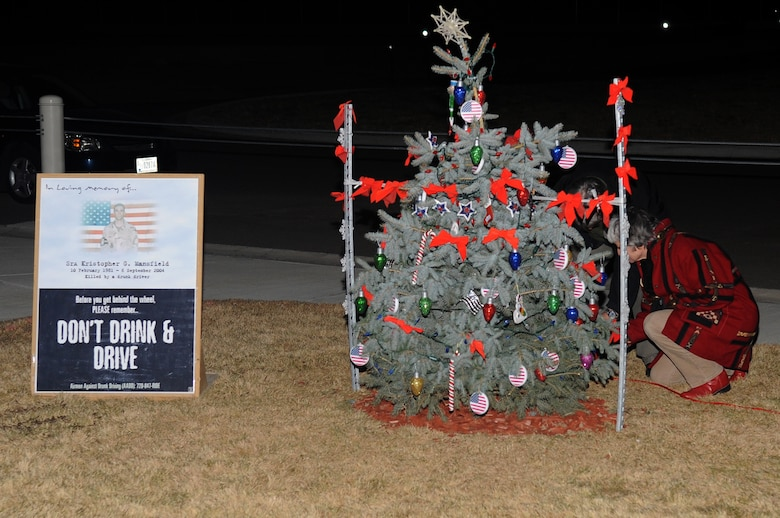 BUCKLEY AIR FORCE BASE, Colo.-- The parents of Senior Airman Kristopher Mansfield light a tree at the 460th Space Communications Squadron on Dec. 14, 2010. Airman Mansfield was killed by a drunk driver in 2004. (U.S. Air Force photo by Airman Manisha Vasquez)