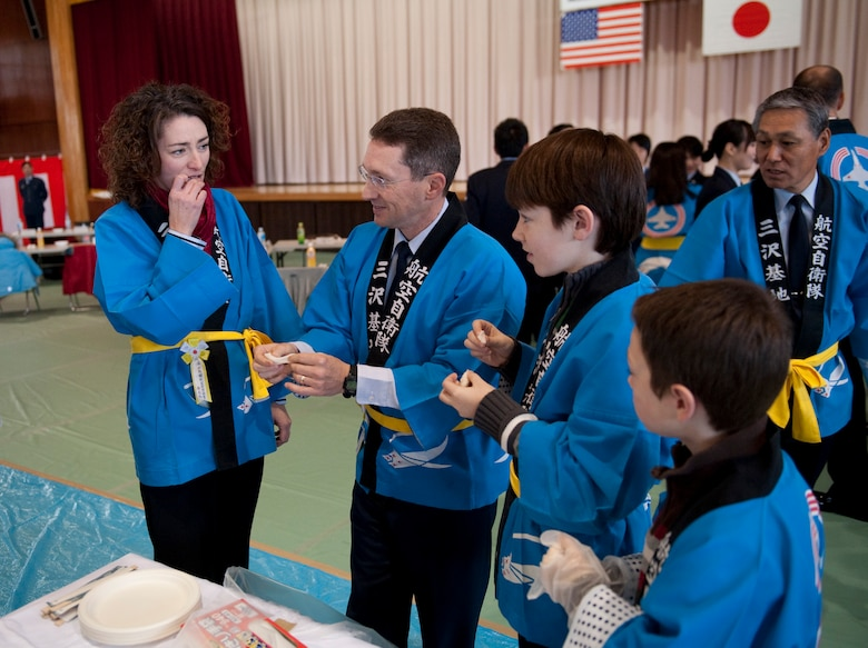 The Rothstein family tries freshly made mochi during the annual mochi pounding ceremony at the Japan Air Self-Defense Force gym, Misawa Air Base, Japan; Dec. 16, 2010. After taking turns pounding steamed rice into the traditional Japanese rice cakes, local dignitaries and their families were able to try the mochi. (U.S. Air Force photo by Staff Sgt. Samuel Morse/Released)