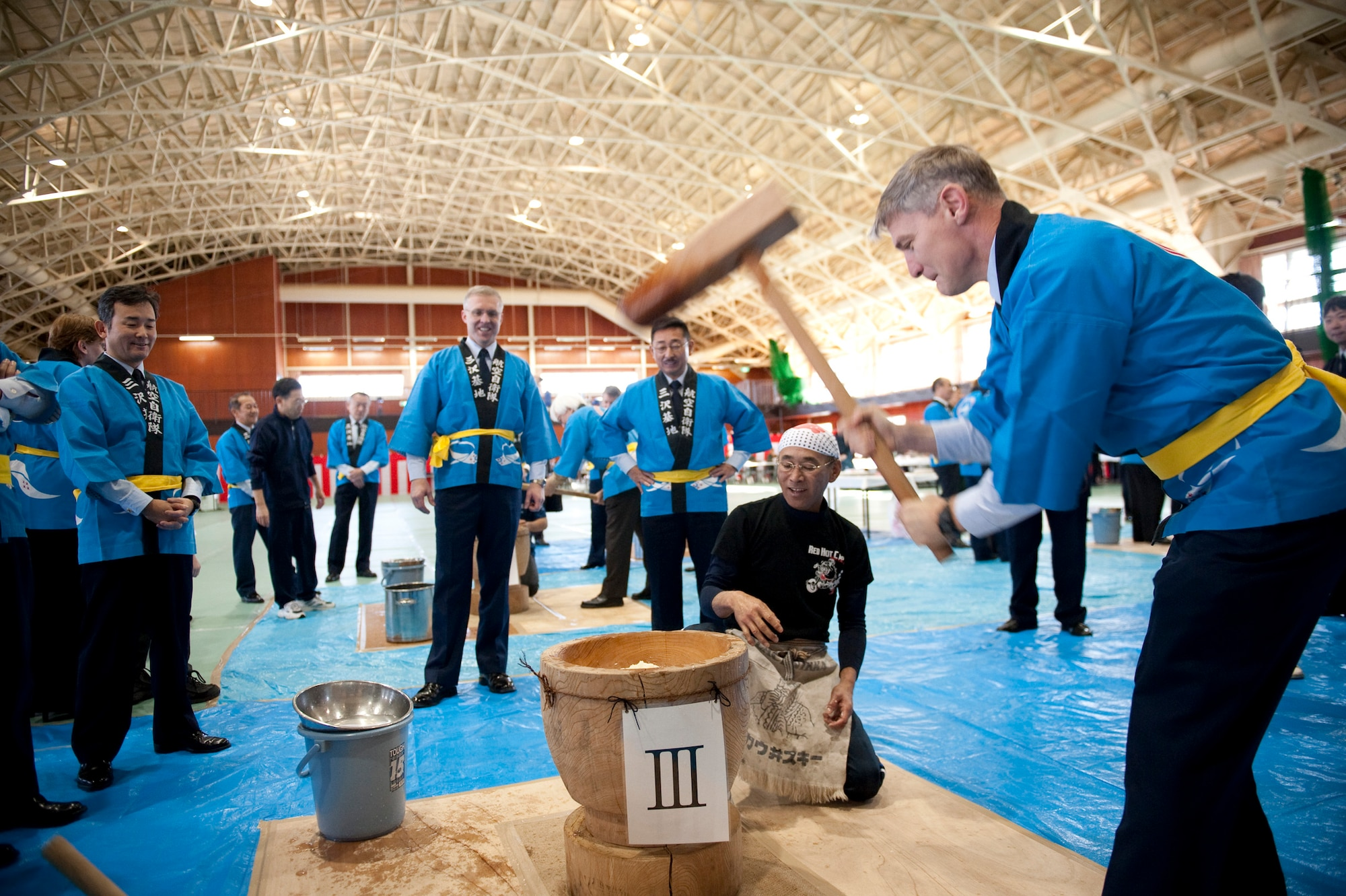 U.S. Air Force Col. John Pearse, 35th Operations Group commander, pounds mochi during the annual mochi pounding ceremony at the Japan Air Self-Defense Force gym, Misawa Air Base, Japan; Dec. 16, 2010. Mochi is a type of rice cake made by pounding steamed, glutinous rice in a large wooden mortar with a large wooden mallet. (U.S. Air Force photo by Staff Sgt. Samuel Morse/Released)