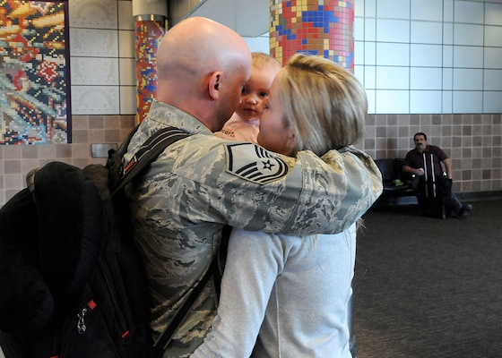 Master Sergeant Brian Thornton is introduced to his four-month-old daughter Kylie as he holds wife Victoria upon returning home from Afghanistan. The baby girl was born while MSgt. Thornton was on a six-month deployment to Kandahar. The homecoming took place at San Antonio International Airport. MSgt. Thornton returns to the 902nd Contracting Squadron at Randolph Air Force Base.  (U.S. Air Force photo/David Terry)