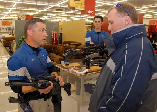 Maj. Steve Dennis, Air Force Action Shooting Team captain, shows a Colt Law Enforcement Military Use AR-15 rifle to Greg Hoffman, 28th Test and Evaluation Squadron, at the shooting display at the base exchange.  (U.S. Air Force photo/Kevin Gaddie)
