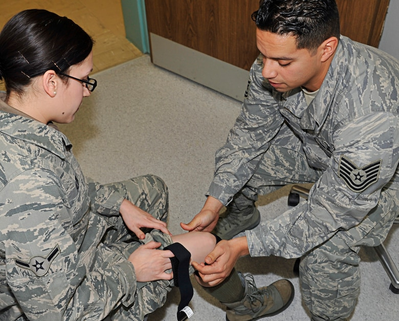 U.S. Air Force Tech. Sgt. Pompilio Alfaro Jr., Landstuhl Regional Medical Center (LRMC), orthotic technician, instructs Airman Kendra Alba, 86th Airlift Wing Public Affairs photographer, on how to properly wear a patella tendon strap, LRMC, Germany, Dec. 15, 2010. (U.S. Air Force photo by Airman 1st Class Desiree Whitney Esposito)