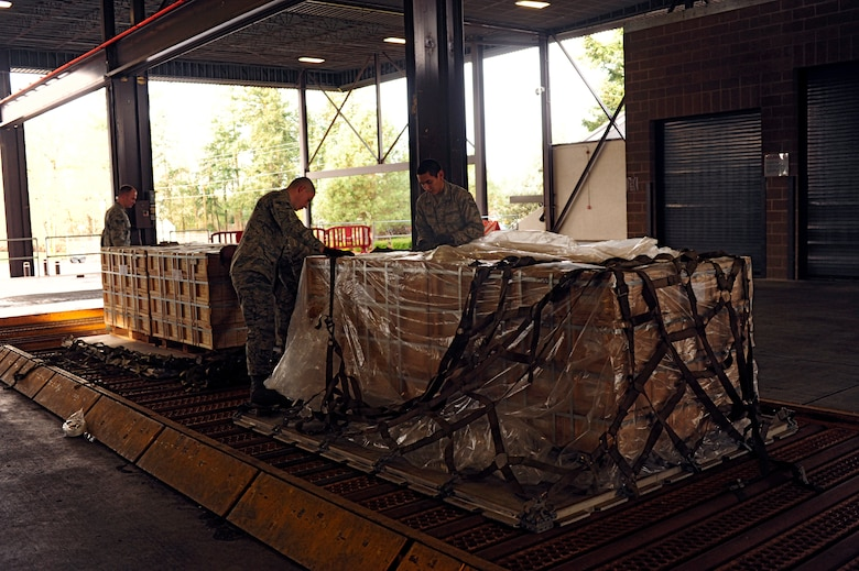 Airmen assigned to the 62nd Aerial Port Squadron secure ammo to pallets before loading it onto a C-17 Globemaster III Dec. 15 at McChord Field, Joint Base Lewis-McChord, Wash. The ammo will be delivered to the Middle East for missions supporting Operation Enduring Freedom. (U.S. Air Force photo/Adamarie Lewis-Page)