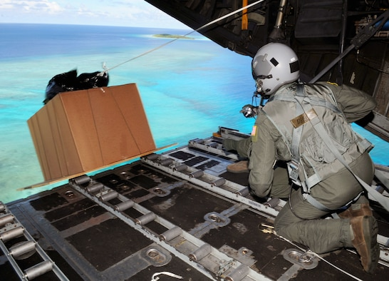 """Senior Airman Joseph Doria and Capt. Stanley Kimball watch after pushing a box of humanitarian assistance goods out of a U.S. Air Force C-130 Hercules, call sign """"Santa 23"""" to its drop-zone in Yap Islands during Operation Christmas Drop, Dec. 14, 2010. This year more than 60 boxes will be dropped to 55 Island weighing in at more than 20,000 pounds.Airman Doria is a 36th Airlift Squadron loadmaster from Yokota Air Base, Japan. Captain Kimball is the 36th Airlift Squadron flight surgeon. (U.S. Air Force photo/Senior Airman Nichelle Anderson)"""