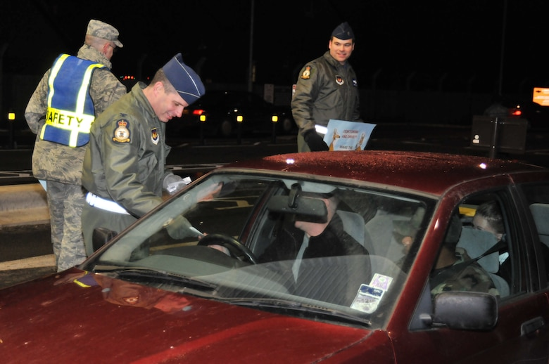 ROYAL AIR FORCE LAKENHEATH, England -- Col. William Lewis, 48th Fighter Wing vice commander, hands out safety cards to motorists arriving on base Dec. 17. The 48th FW Safety office encourages all drivers to practice safe driving habits this holiday season. (U.S. Air Force photo/Senior Airman David Dobrydney)