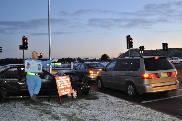 ROYAL AIR FORCE LAKENHEATH, England – Larry the Crash Dummy reminds departing Lakenheath motorists to be careful Dec. 17 at the Lakenheath main gate. The 48th FW Safety Office encourages all drivers to practice safe driving habits this holiday season. (U.S. Air Force photo/Senior Airman David Dobrydney)