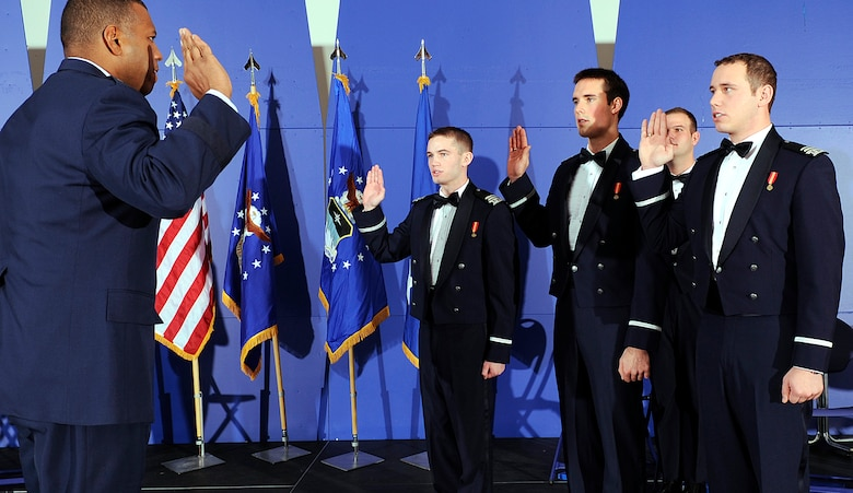 State your name: Brig. Gen. Richard Clark administers the oath of office to Cadets 1st Class Mikhail Fedorchik, Andrew Herzog and Sean Lipkin before the three receive their commissions as second lieutenants during a graduation ceremony at the Air Force Academy Dec. 15, 2010. In the background is Cadet 1st Class Mathew Haxton, one of three cadets who graduated without receiving commissions. (U.S. Air Force photo/Mike Kaplan)