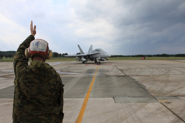 Lance Cpl. Kent Hinderleider, Marine All-Weather Fighter Attack Squadron 225 aviation ordnance technician, guides a VMFA(AW)-225 F/A-18 Hornet to a parking point on the runway for an ordnance check here Dec. 17. Hinderleider was the team leader for this particular check. As the team leader, Hinderleider used only hand and arm signals to direct his team of technicians and the pilots through the safety check.