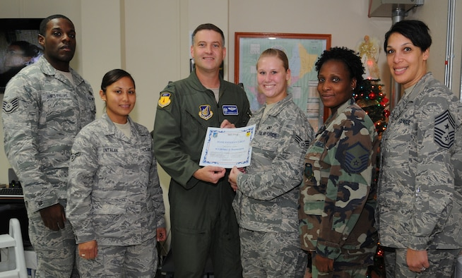 Senior Airman Britney Hammergren (center), 36th Wing Command Post senior controller, stands with her peers after being awarded Andersen's Best here Dec. 9.