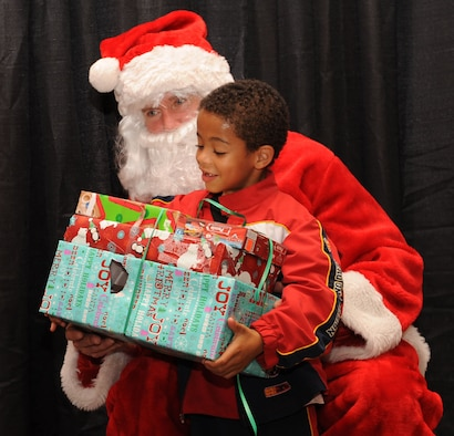 Jacob Thrasher, 6, receives presents from Santa Claus during the Santa's in Blue event at the Bossier City Civic Center in Bossier City, La., Dec. 18. Santa's in Blue is a program sponsored by the Air Force Sergeants Association and Barksdale Top Three to provide gifts for more than 400 children in foster care. (U.S. Air Force photo/Airman 1st Class Sean Martin)(Released)