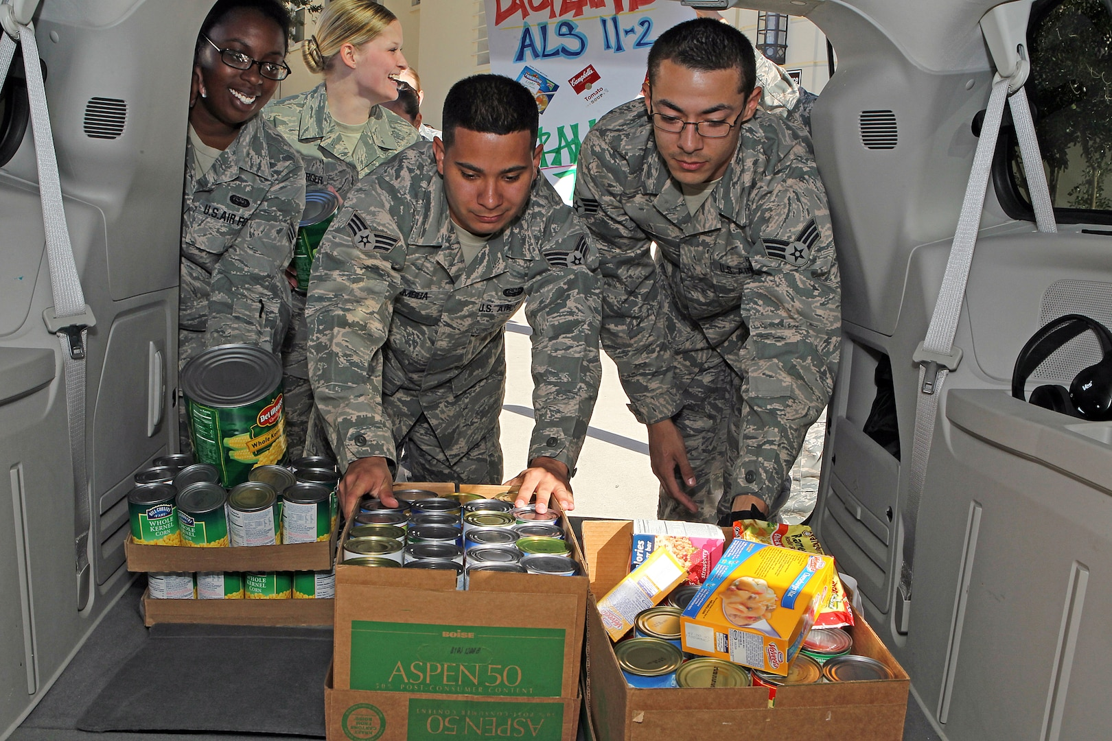 Senior Airmen Jeanette Collins, Jeremy Cook and Danny Gamboa load a van Dec. 9 with food items collected by Airman Leadership School for the San Antonio Food Bank. Members of ALS Class 11-2 collected more than 1,100 pounds of food to support needy families in the community. (U.S. Air Force photo/Antonio Morano)